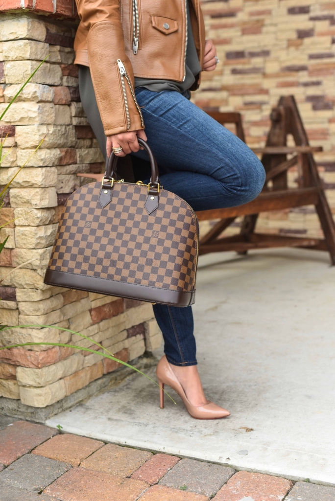 Luxury Handbag Collection and Review featured by top US fashion blog, LuxMommy: image of a woman wearing a Louis Vuitton Alma MM Ebene