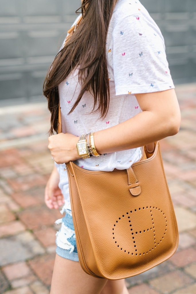 Luxury Handbag Collection and Review featured by top US fashion blog, LuxMommy: image of a woman wearing a Hermes Evelyne PM Gold