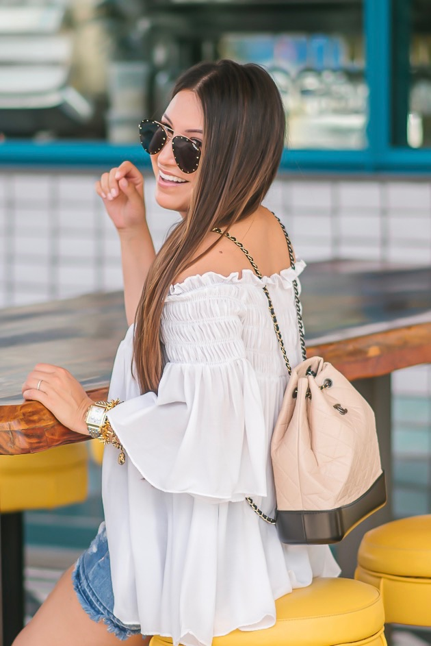 Luxury Handbag Collection and Review featured by top US fashion blog, LuxMommy: image of a woman wearing a Chanel Gabrielle Backpack