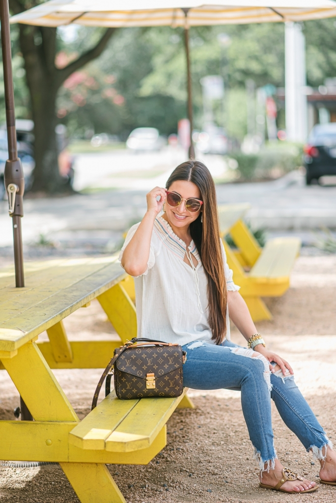 Rainbow smocked top styled for summer by top US fashion blog, LuxMommy: image of a woman wearing a Madewell rainbow smocked top, Express mid rise jeans, Tory Burch flip flops, Kendra Scott drop earrings, Michele diamond watch, Stella & Dot spike bracelet and Louis Vuitton crossbody bag.