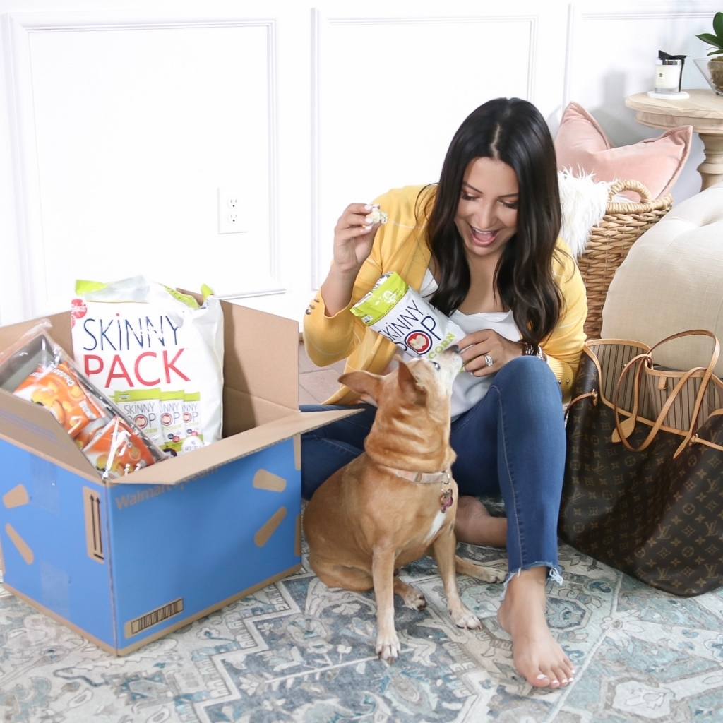 How to Get Household Essentials with Walmart Next Day Delivery by popular Texas life and style blog: Lux Mommy: image of a woman holding a bag of Skinny Pop popcorn and sitting on her floor next to her dog and a Walmart next day delivery box.