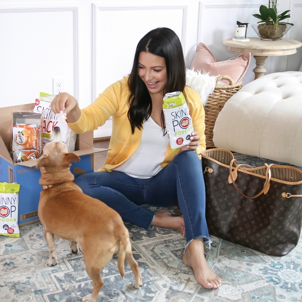 How to Get Household Essentials with Walmart Next Day Delivery by popular Texas life and style blog: Lux Mommy: image of a woman sitting on her floor, holding a bag of Skinny Pop and feeding it to her dog.