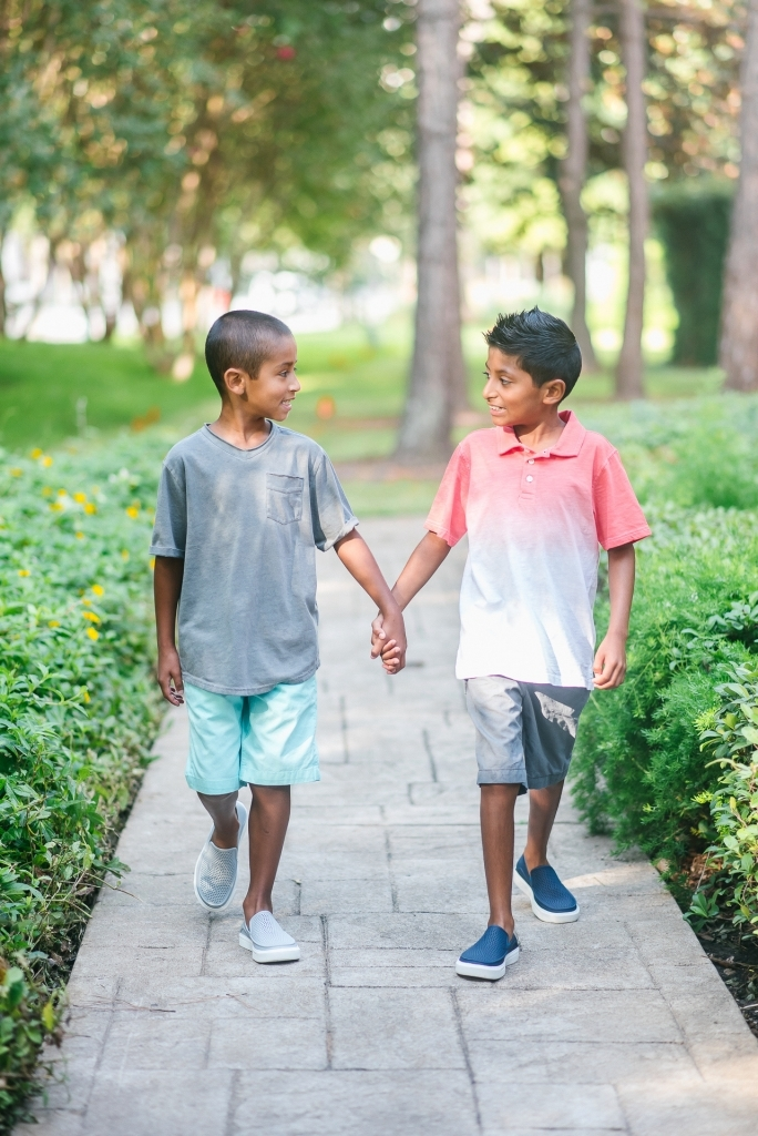 Back to School Style with Walmart by popular Texas fashion blog, Lux Mommy: image of two boys holding hand and walking on a brick pathway outside and wearing a Walmart Wonder Nation Short Sleeve Ombre Jersey Polo, The Children's Place Pull On Woven Jogger Short, and Crocs Unisex Junior CitiLane Roka Shoes.