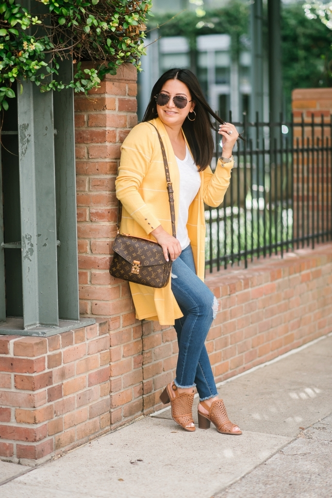 Affordable Fall Transitional Outfit by popular Texas fashion blog, Lux Mommy: image of a woman leaning up against a brick building and wearing a Walmart Heart N Crush Women's Long Striped Cardigan, Clementine Apparel Women's Deep V-Neck Short Sleeve T-Shirt, Sofia Jeans by Sofia Vergara Sofía Skinny Destructed Mid Rise Ankle Jean Women's (Medium Wash), and Women Big Buddha Woven Peep Toe shoe.